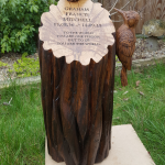 Oak stump memorial with hand carved woodpecker